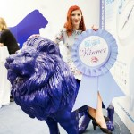 Betty Hobcraft sitting on a blue lion after winning the Start Up Hub 2012